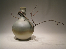 twist necked ikebana vase with stick
